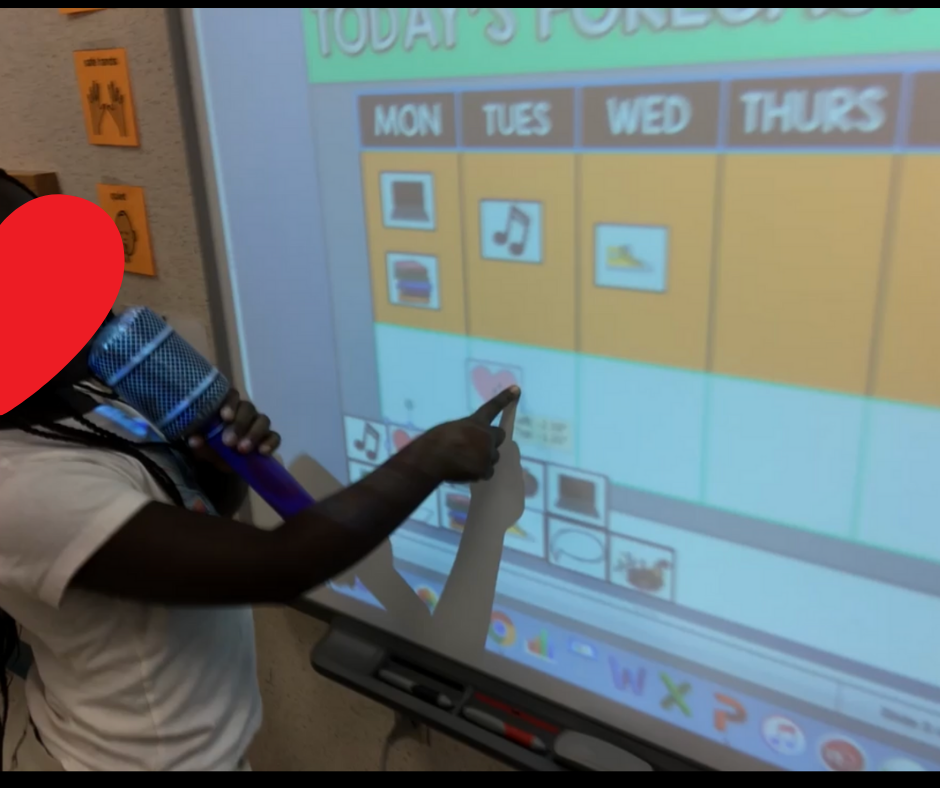 A student pointing to the whiteboard with an inflatable microphone.