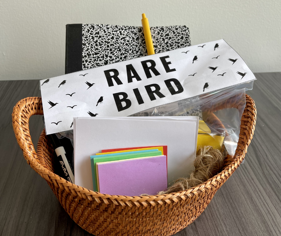 Basket with morning meeting supplies including notebook, Rare Bird materials, sticky notes, twine, and a marker